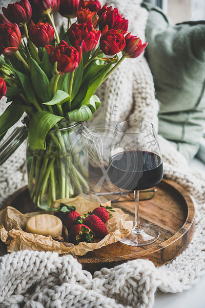 Glass of red wine, snacks and spring red tulips
