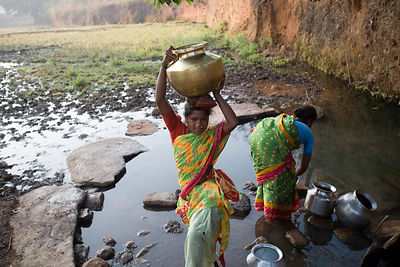 A tribal woman carries water