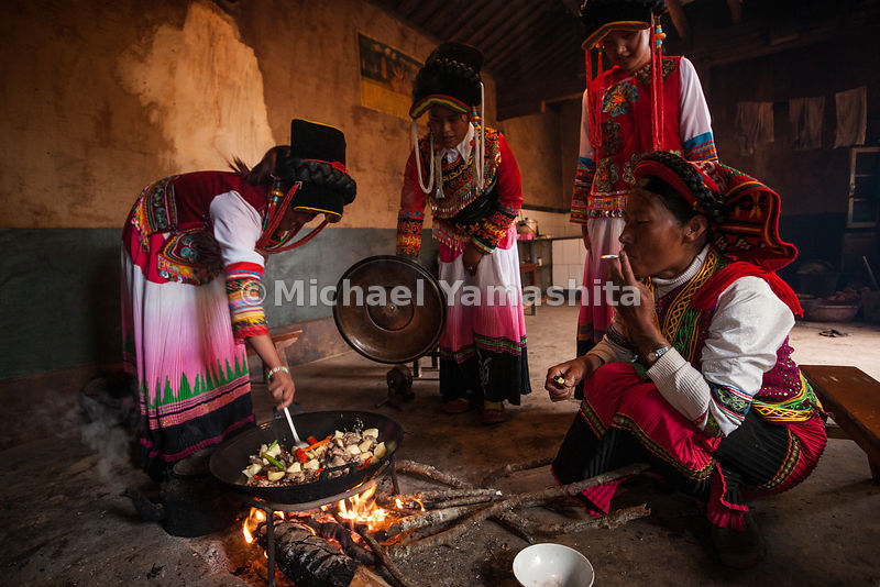 Yi women, known for their colorful and distinctive costumes, prepare a meal in their village near Shaxi. They are among the 4...
