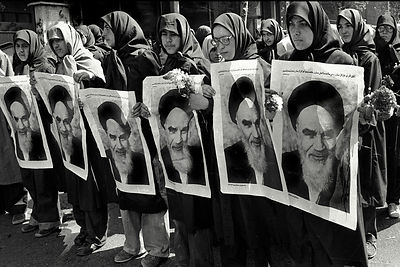 Iranian women marching with portraits Ayatollah Ruhollah Khomeini the founder of Iran's 1979 Islamic revolution in Tehran 1980..