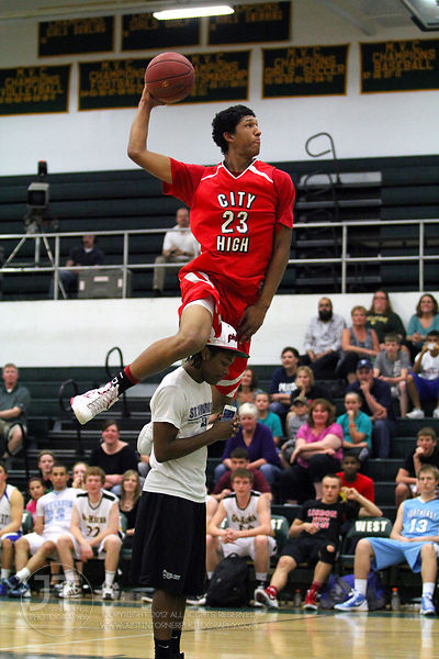 Iowa CIty High's Jerel Moore jumps over Richard Bryant of Iowa City West High in the slam dunk competition. The Northern All-...