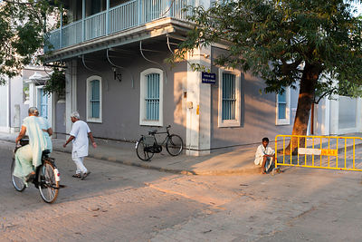 A man sits in the road waiting for work as a woman and a man exercise shortly after dawn. Pondicherry, India