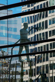 Sculpture of a man on stilts sruuounded by buildings in Santiago, Chile.