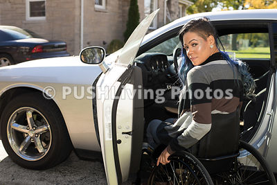 Young woman in a wheelchair getting into her car