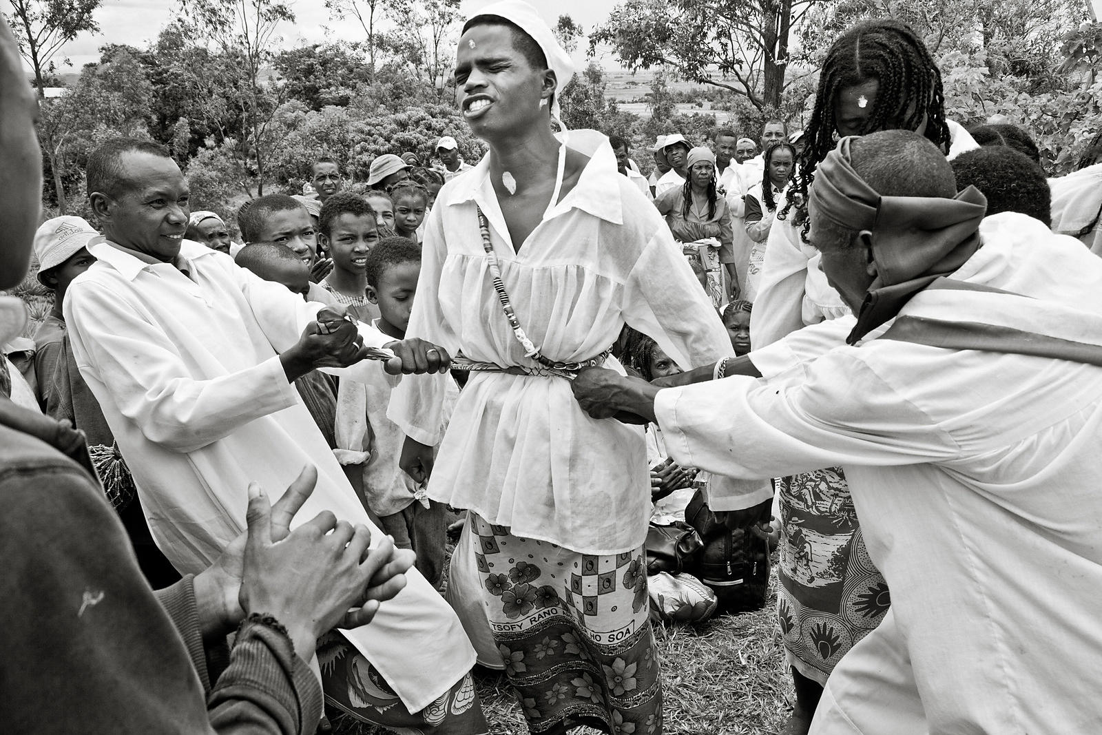 "MANGALAZA COMMUNE - ""Mpanazary"" in the middle of a trans session. They are members of the ANTALAOTRA association, the largest cultural association in this part of Madagascar, whose mission is to promote and make known the rites, cults and traditions of the Alaotra Mangoro region, a sacred region according. Created in 2014, the association already has 37,000 members. Most of them are Mpanazary that can be translated as spiritual guide, diviner, medium. The literal translation is ""bewitching"". The Mpanazary are almost considered as "" demi-gods "". Their dreams, predictions and premonitions are respected and followed by the people of the region and even by the civil and administrative authorities. The region around Lake Alaotra (North-East of Madagascar) is one of the richest agricultural regions in Madagascar. It is considered the ""rice granary"" of the Big Island. Some argue without hesitation that it is because of the sacred character of the region and its particular cultural practices that the region is so prosperous. Today, as every year, the local population and some Mpanazary go to a sacred hill near the village of Mangalaza to invoke the spirits of the ancestors (Tromba) and ask Zanahary (animist Malagasy God) and Andriamanitra (Christian God) to kindly bring again the beneficial rains for next October that will grow the crops. Each Mpanazary has its specialty: some can bring rain, some can stop cyclones, others can drive out evil spirits. The patients take the opportunity to be treated by the Mpanazary-healer. ."
