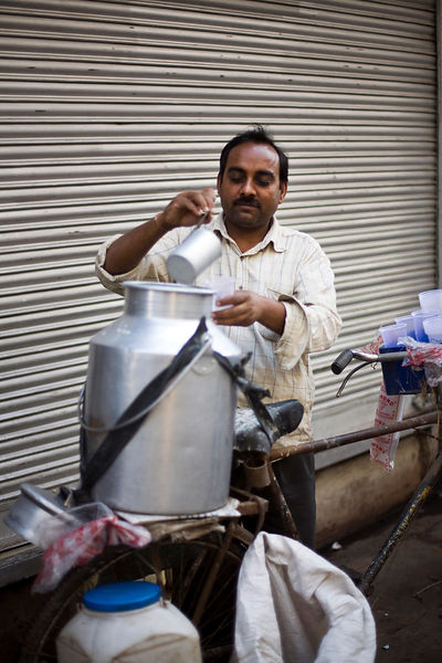 India - Delhi - A man pours buttermilk from his churn on a bicycle in Chadni Chowk,