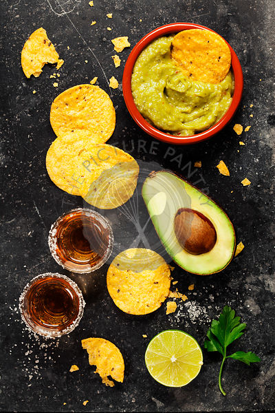 Bowl of mexican nachos chips with homemade fresh guacomole sauce and tequila shots over old  background. Top view. With space...