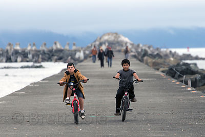 Children ride bikes on a pier in Crescent City, California