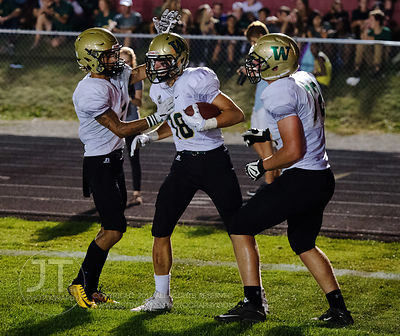 Iowa City West's Cole Mabry (18) celebrates with teammates after he runs in for a touchdown on Iowa City High during the firs...