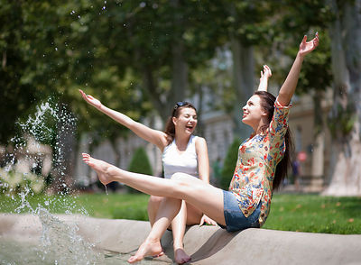 Young women splashing in a fountain