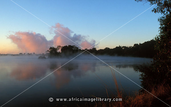 Zambezi river above Victoria Falls at sunrise with the spray of the waterfall visible in the distance, Victoria Falls Nationa...