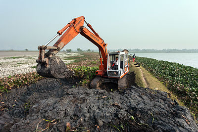 A backhoe excavates soil in the East Kolkata Wetlands, Kolkata, India. The purpose of the work could not be established.