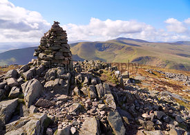 The summit cairn (pile of stones) of Carrock Fell with Bowscale Fell and Blencathra in the distance in the English Lake Distr...