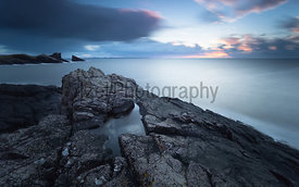 A long exposure of Split Rock at Clachtoll Bay as the sun sets over the Scottish Highlands.