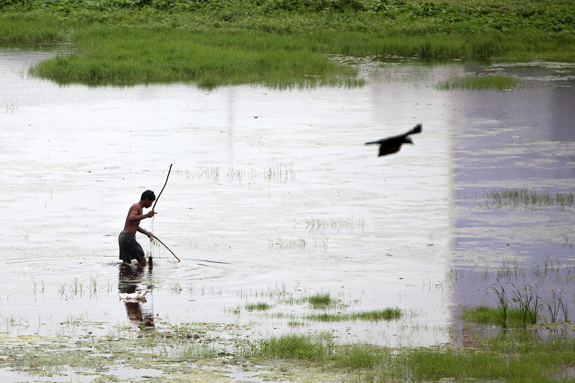 A man fishes in a heavily polluted makeshift wetland near the Bandra Railway Station, in the heart of urban Mumbai, India.