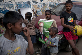 A young boy hold a poster of Paul RABARY, a candidate in the first round of the Malagasy presidential election, in the Manjak...