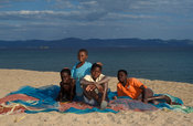 children sitting on fishing nets on the beach, Likoma Island, Lake Malawi, Malawi