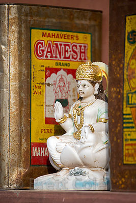 Marble statuette of Saraswati next to metal boxes holding mustard oil, Budha Pushkar, Rajasthan, India
