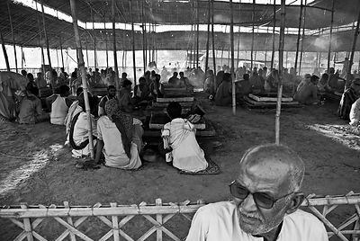 This portrait of an old man was shot during the Kumbh Mela. In the background the pilgrims wait for the Havan ceremony to sta...