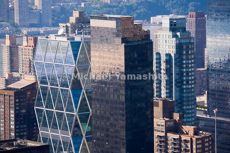 The triangles of the Hearst Tower's exo-skeleton are a stark contrast to the rectangular design of its neighbor, the Time Warner Towers.  Manhattan, New York City.