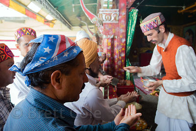 A man in a star spangled headwrap prays at a Hindu temple during the celebration of Dussehra in Kullu, India