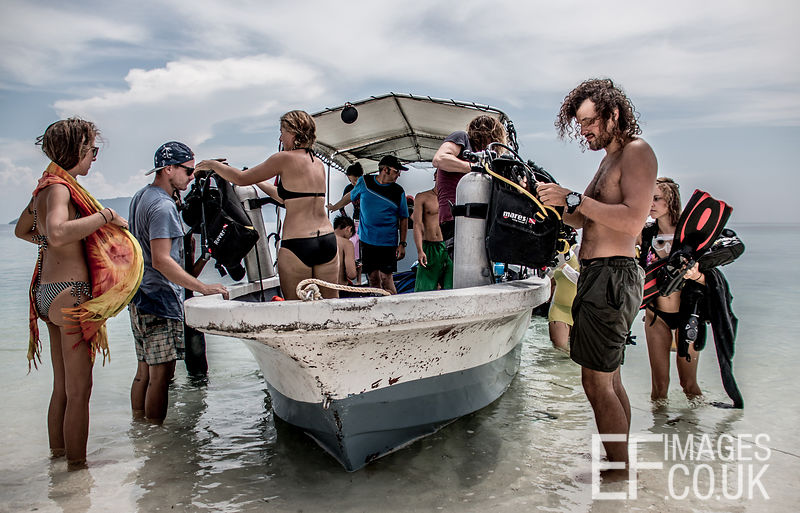 Divers Unloading A Dive Boat On A Tropical Beach