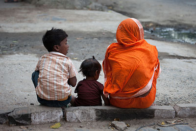 A family rests on a curb on Strand Road, Kolkata, India.