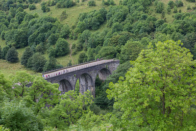 Walkers and cyclists on the Headstone Viaduct, which crosses Monsal Dale and the River Wye, and is part of the Monsal Trail c...