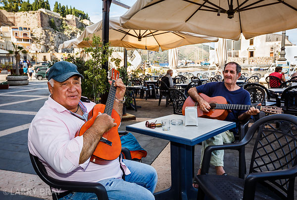 Two local musicians playing guitar at a cafe in Lipari, Italy
