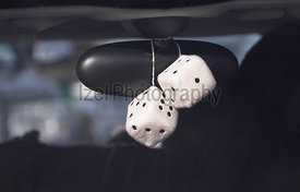 Fluffy dice hanging off the rear view mirror of a car.