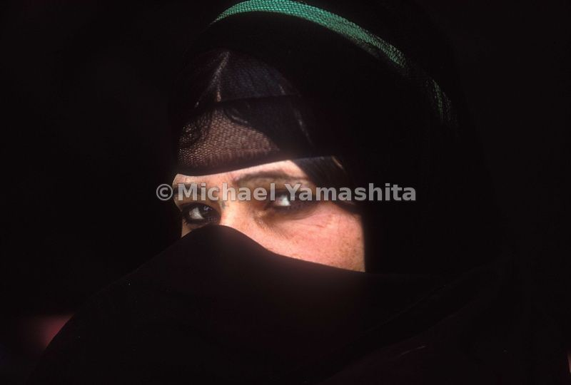 A woman covers half of her face with a veil in Iraq.