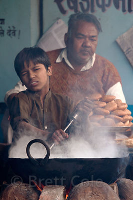A boy winces at hot steam from his wok, Pushkar, Rajasthan, India
