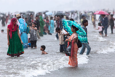 Families recreate in the Arabian Sea during monsoon rains at Juhu Beach, Mumbai, India. Juhu is a popular family destination ...