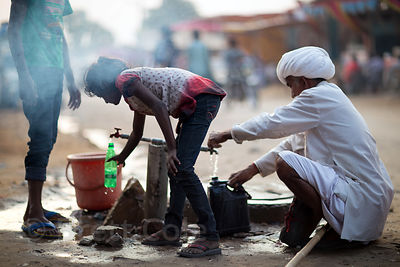 People fill water vessels at a pump on the Pushkar mela grounds, Pushkar, Rajasthan, India