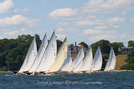 A flock of S-boats charge across the starting line in front of Popasquash Point houses at the 2005 Herreshoff Rendezvous.