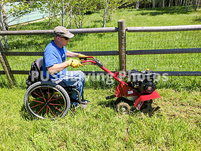 Man using a wheelchair using a rotary hoe