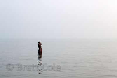 A man bathes and prays in the Bay of Bengal during the Gangasagar Mela, Sagar Island, India.