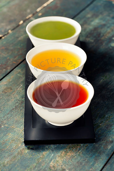 Tea concept. Different kinds of tea (black, green and matcha tea) in ceramic bowls on wooden background
