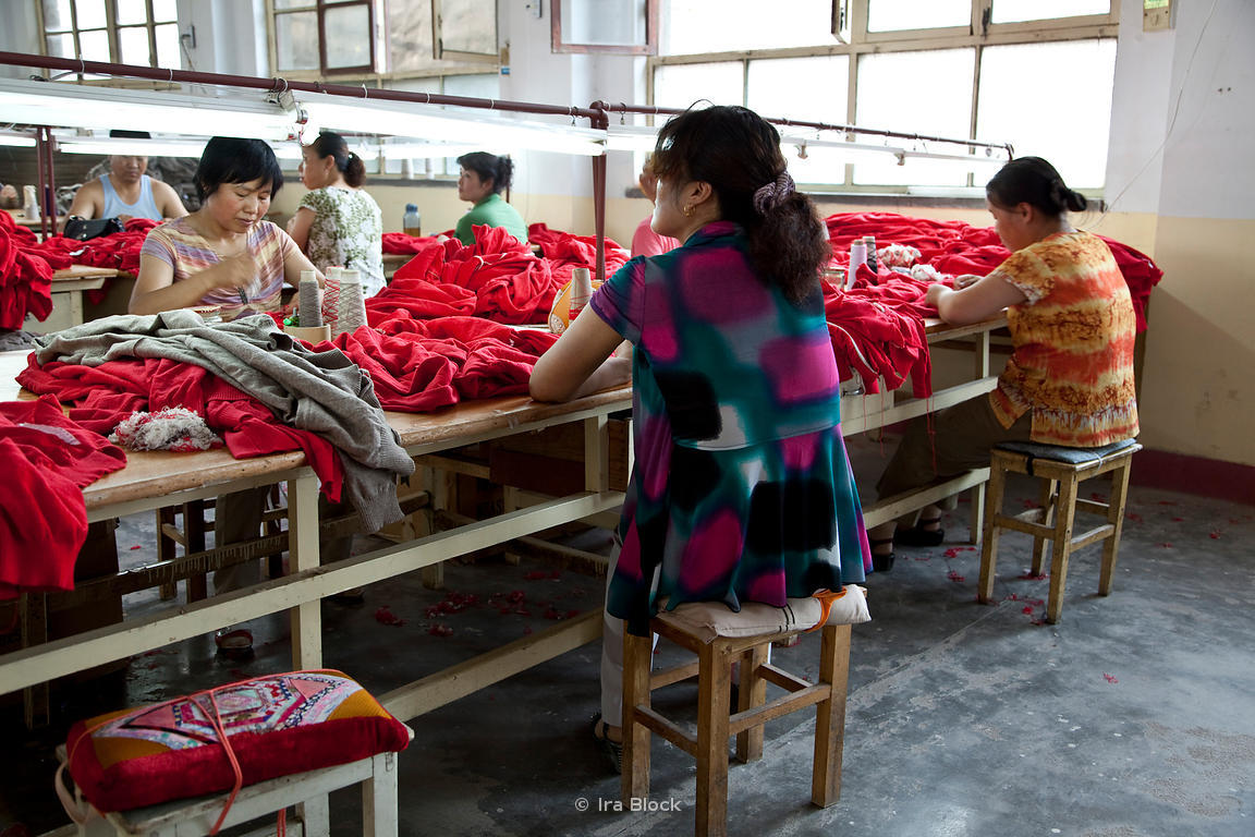 Women sit at their sewing stations where they perform their daily tasks at a cashmere sweater factory in Qi Shan, China.