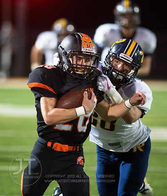 Solon's Hunter Kula (28) is brought down by Iowa City Regina's Ryan Schott (28) after a long run during the first half of pla...
