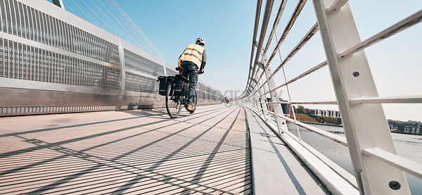 GATESHEAD, ENGLAND, UK - MAY 08, 2018: A cyclist and Pedestrians crossing the Gateshead Millennium Bridge