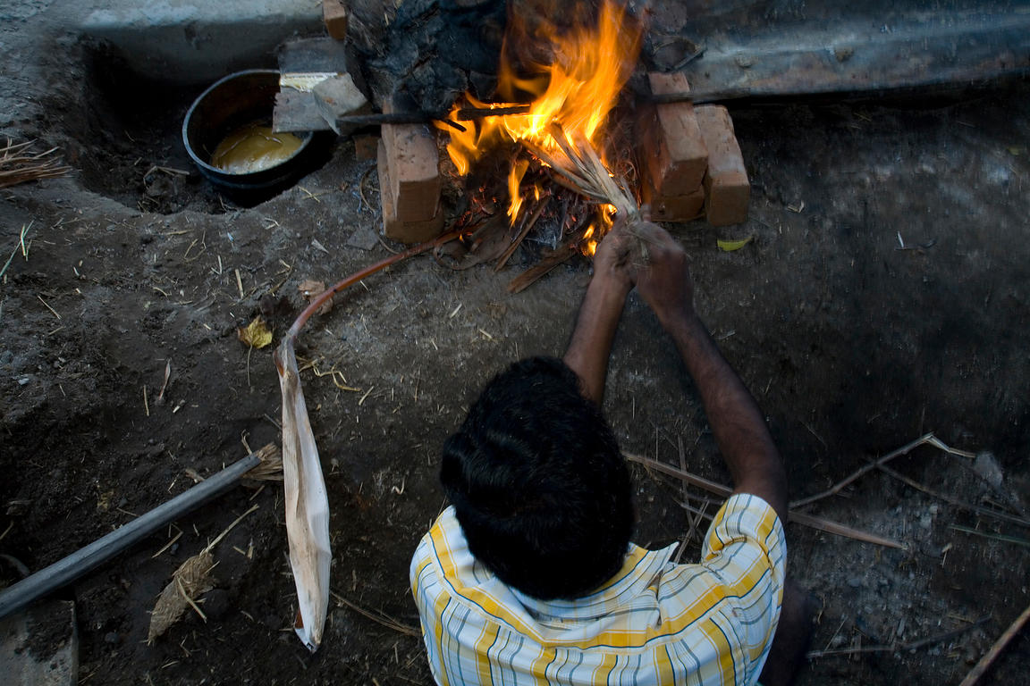 India - Swamimalai - A worker tends the fire that will melt the wax for casting in the pit at the workshop