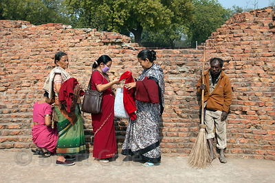 A humble Hindu worker stands next to Buddhist pilgrims at the Sarnath Archaeological Site, Sarnath, India.