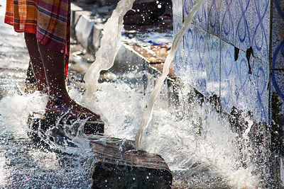 A man bathes in a spigot on the street in Sovabazar, Kolkata, India.