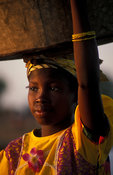 Peul girl carrying her dishes to wash up to the river, Djenné, Mali