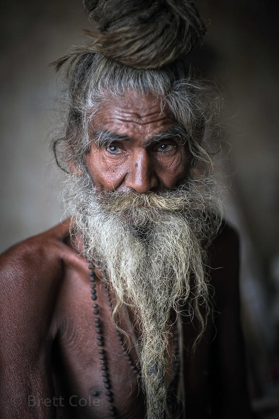 Elderly sadhu in his hut on the ghats of Pushkar Lake, Pushkar, Rajasthan, India. Natural light and background.