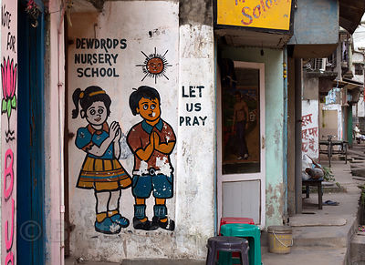 Children pray on a painting on the outside of a nursery school, Salkia, Howrah, India