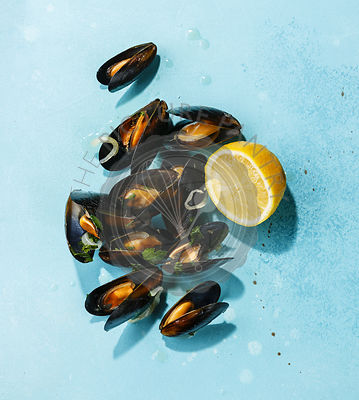 Mussels and lemon on blue background