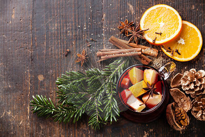 Cup of hot wine with spices on wooden background