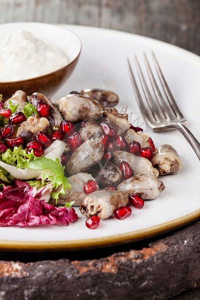 Fried chicken hearts with lettuce and pomegranate